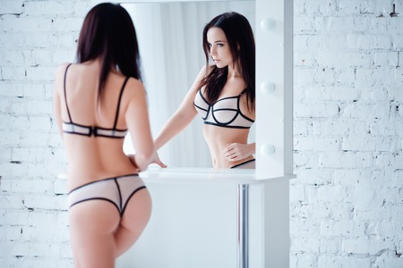 erotic women: Perfect, sexy body and ass of young woman wearing seductive lingerie. Beautiful hot female in lacy underware posing close to mirror.