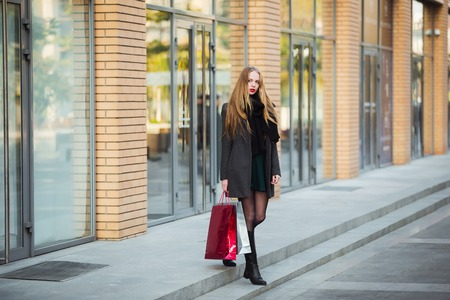 consumerism: Sale, consumerism and people concept - happy young beautiful women holding shopping bags, walking away from shop Stock Photo