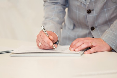 Cropped view of businessman signing a contract. Man hand with pen close up