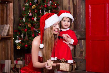 decorate: Two Santa girls decorating Christmas tree having fun. New year interior. Xmas atmosphere, family celebrating holidays