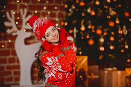 red cardigan: Winter, xmas portrait: Young woman dressed in red warm woolen cardigan, gloves and hat posing indoor near Christmas tree.