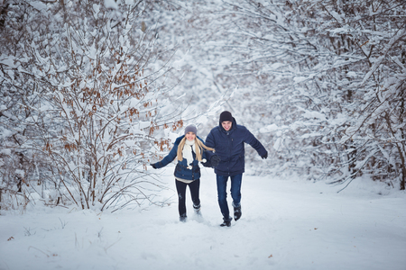 winter vacation: Happy Couple Having Fun Outdoors in Snow Park. Winter Vacation.