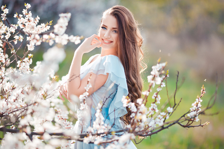 Resorte sonrisa. hermosa mujer joven y sonriente feliz en el parque de la flor. Foto de archivo