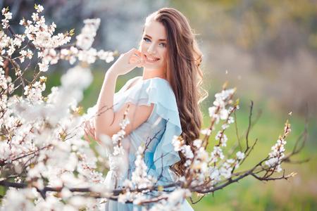 spring. Gelukkige mooie glimlachende jonge vrouw in de bloei park.