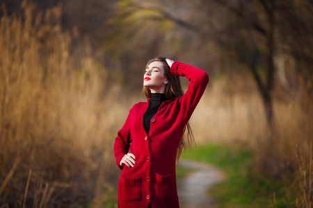 Dreaming young woman. Beautiful female with long healthy hair enjoying nature in park wearing red cardigan. Spring, autumn portrait. Stock Photo