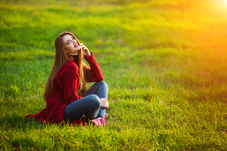 Happy young woman. Beautiful female with long healthy hair enjoying sun light in park sitting on green grass. Spring, autumn portrait.