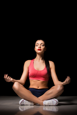 Portrait of happy sporty woman relaxing in lotus position. Joyful female model breathing fresh air indoors. Healthy active lifestyle and yoga concept. Stock Photo