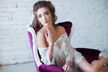 Perfetto, corpo sexy, gambe e culo di giovane donna che indossa lingerie seducenti. Sensuale ragazza posa sul divano in modo erotico
