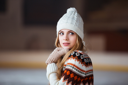 Autumn, Winter portrait: Young smiling woman dressed in a warm woolen cardigan, gloves and hat posing outside.