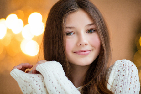 Portrait of beautiful girl with long hair wearing warm winter clothes in Christmas interior.