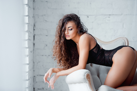 Perfect, sexy body, legs and ass of young woman wearing seductive black lingerie. Beautiful hot female in bodysuit posing on luxury vintage chair