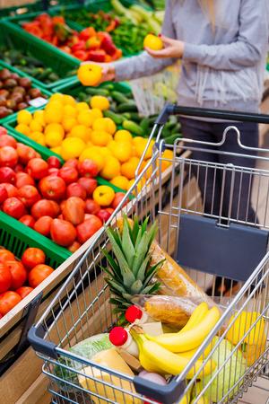 Conceito de consumismo. Mulher fazendo compras no supermercado Foto de archivo - 94344689