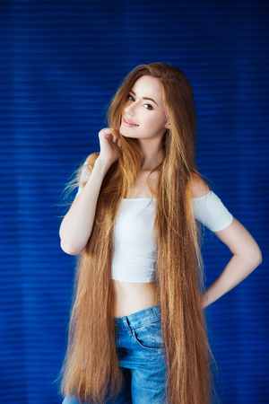 Young beautiful woman in a white shirt and jeans with very long natural hair near a blue wall in loft interior