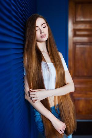 다락방 인테리어에 파란색 벽 근처에 매우 긴 자연 머리와 흰 셔츠와 청바지에 젊은 아름 다운 여자