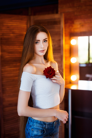 Young beautiful woman in a white shirt and jeans with very long natural hair holding a rose flower in loft interior