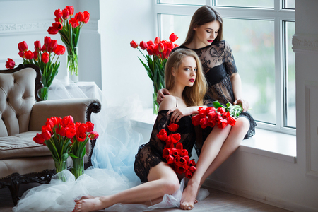 Fashion models in tender black lingerie posing in sensual way at luxury interior full of tulips. Young woman sensuality.