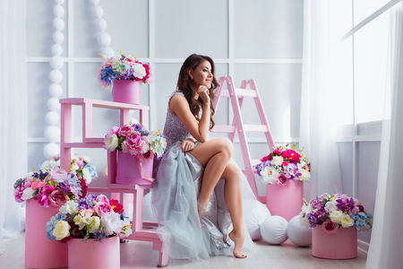 Attractive young woman in elegant dress sitting in studio interior decorated with flowers. Beautiful fresh smiling girl posing with flowers