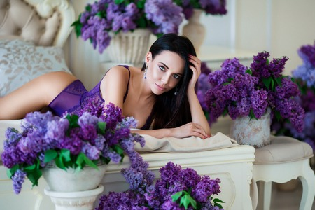 Young, sexy woman with hot body posing in lingerie at luxury interior in bed close to violet flowers.