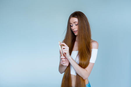 Concept of hair loss. Close up portrait of unhappy sad stressed young woman with long dry brown hair, she is looking at the brush in hand, isolated on grey background.