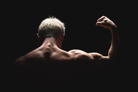 Handsome power athletic man in dramatic light. Strong bodybuilder with perfect shoulders, biceps, triceps, back, delta and chest. Strength and motivation. Bottom view.