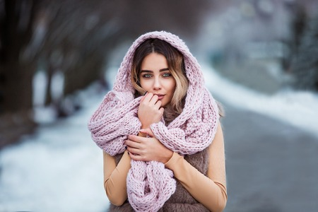 Winter portrait: Young pretty woman dressed in a warm woolen clothes, scarf and covered head posing outside. Standard-Bild - 112972372