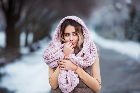 Winter portrait: Young pretty woman dressed in a warm woolen clothes, scarf and covered head posing outside. Standard-Bild - 112972373