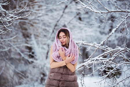 Winter portrait: Young pretty woman dressed in a warm woolen clothes, scarf and covered head posing outside. Standard-Bild - 112972376