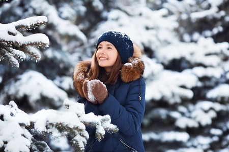 Winter portrait: Young pretty girl dressed in a warm woolen clothes, scarf and covered head posing outside. Standard-Bild - 112972378