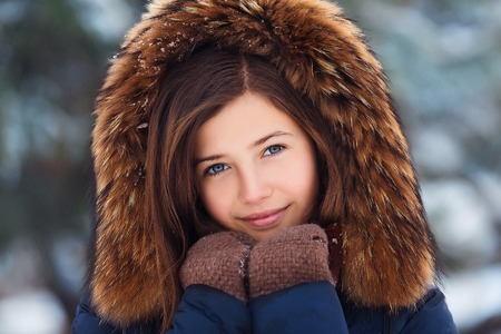 Winter portrait: Young pretty girl dressed in a warm woolen clothes, scarf and covered head posing outside. Standard-Bild - 112972379