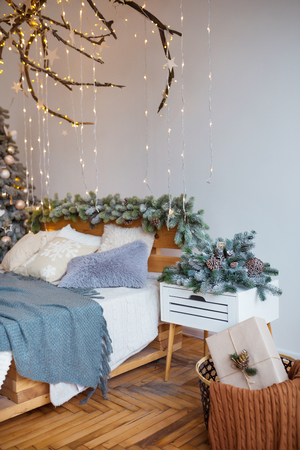 White cozy modern bedroom with holiday decoration. Wooden bed in scandinavian style room with festive Christmas tree in a pot and led garland lights. Home christmas decor. Standard-Bild - 112972388