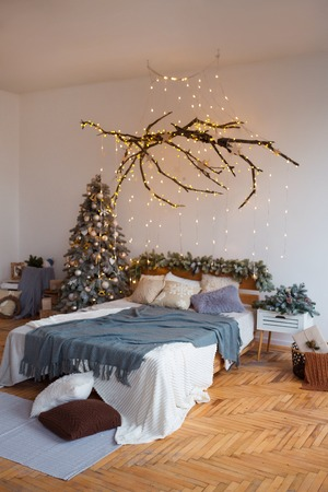 White cozy modern bedroom with holiday decoration. Wooden bed in scandinavian style room with festive Christmas tree in a pot and led garland lights. Home christmas decor. Standard-Bild - 112972389