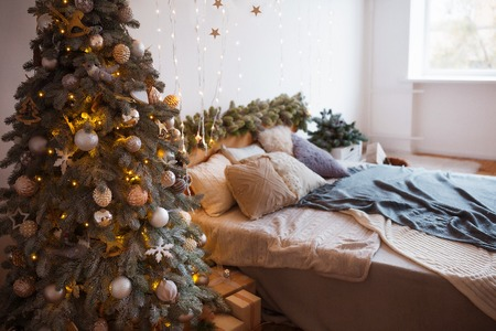 White cozy modern bedroom with holiday decoration. Wooden bed in scandinavian style room with festive Christmas tree in a pot and led garland lights. Home christmas decor. Standard-Bild - 112972391