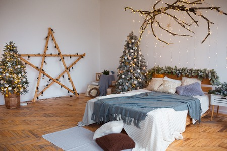 White cozy modern bedroom with holiday decoration. Wooden bed in scandinavian style room with festive Christmas tree in a pot and led garland lights. Home christmas decor. Standard-Bild - 112972392