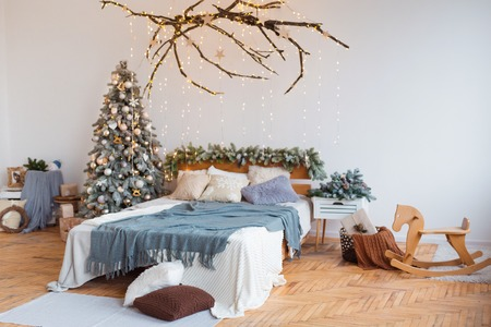 White cozy modern bedroom with holiday decoration. Wooden bed in scandinavian style room with festive Christmas tree in a pot and led garland lights. Home christmas decor. Standard-Bild - 112972520