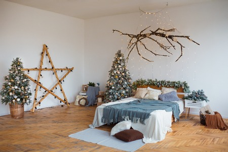 White cozy modern bedroom with holiday decoration. Wooden bed in scandinavian style room with festive Christmas tree in a pot and led garland lights. Home christmas decor. Standard-Bild - 112972522