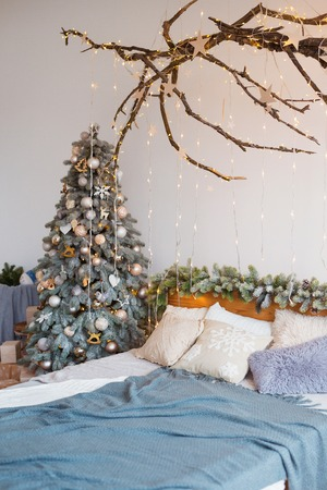 White cozy modern bedroom with holiday decoration. Wooden bed in scandinavian style room with festive Christmas tree in a pot and led garland lights. Home christmas decor. Standard-Bild - 112972528