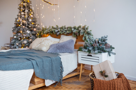 White cozy modern bedroom with holiday decoration. Wooden bed in scandinavian style room with festive Christmas tree in a pot and led garland lights. Home christmas decor. Standard-Bild - 112972529