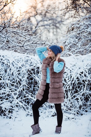 Winter portrait: Young pretty woman dressed in a warm woolen clothes and hat posing outside. Standard-Bild - 112972530