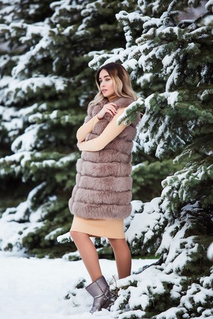 Winter portrait: Young pretty woman dressed in a warm woolen clothes posing outside. Standard-Bild - 112972532
