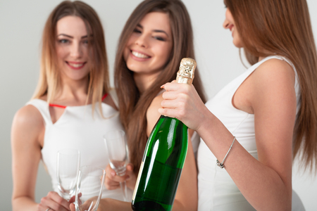 Three young woman in elegant dresses having fun, smiling, dancing and drinking champagne in studio on white background. Christmas party celebration concept. Standard-Bild - 112972550