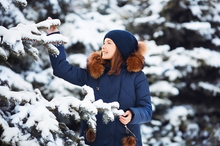 Winter portrait: Young pretty girl dressed in a warm woolen clothes, scarf and covered head posing outside. Standard-Bild - 112972555