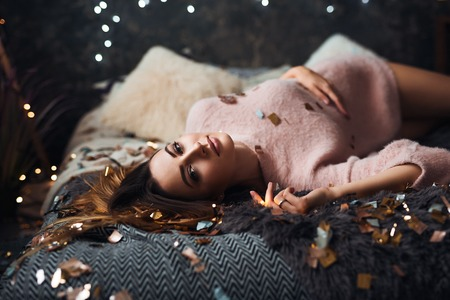 Portrait of attractive young woman with tinsel confetti and garland lights celebrating alone in dark room. New years feeling. Merry christmas Standard-Bild - 112972661