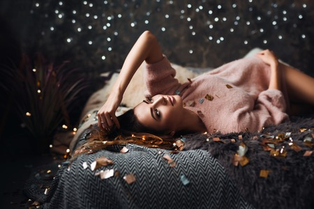 Portrait of sad attractive young woman with tinsel confetti and garland lights celebrating alone in dark room. New years feeling. Merry christmas Standard-Bild - 112972682