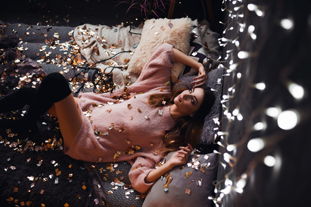 Portrait of sad attractive young woman with tinsel confetti and garland lights celebrating alone in dark room. New years feeling. Merry christmas Standard-Bild - 112972685