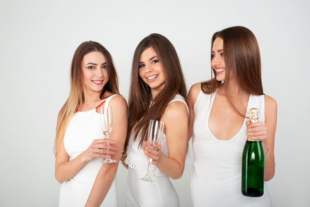 Three young woman in elegant dresses having fun, smiling, dancing and drinking champagne in studio on white background. Christmas party celebration concept. Standard-Bild - 112972686
