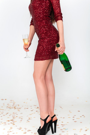 Perfect long legs of young woman in elegant dresses having fun, smiling, dancing and drinking champagne in studio on white background. Christmas party celebration concept. Standard-Bild - 112972687