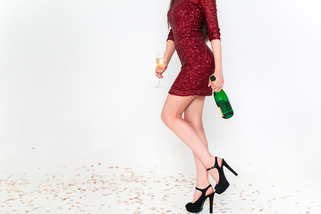 Perfect long legs of young woman in elegant dresses having fun, smiling, dancing and drinking champagne in studio on white background. Christmas party celebration concept. Standard-Bild - 112972688