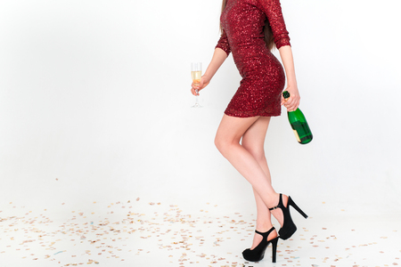 Perfect long legs of young woman in elegant dresses having fun, smiling, dancing and drinking champagne in studio on white background. Christmas party celebration concept. Standard-Bild - 112972689