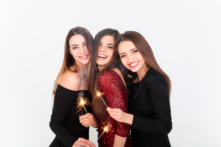 Perfect celebration night concept. Beautiful young women looking at camera and holding sparkler with smile while standing against white background Standard-Bild - 112972692