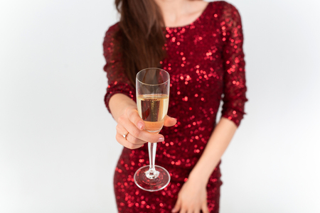 Beautiful brunette woman wearing elegant red dress holding a glass of champagne in her hand on white background Standard-Bild - 112972693